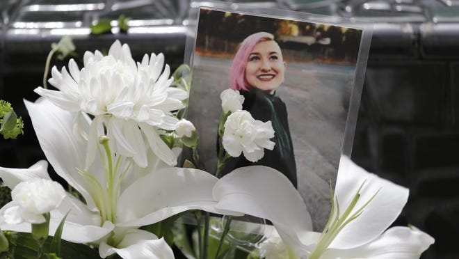 A photo of Summer Taylor, who suffered critical injuries and died after being hit by a car while protesting over the weekend, sits among flowers at the King County Correctional Facility where a hearing was held for the suspect in their death Monday, July 6, 2020, in Seattle. Dawit Kelete is accused of driving a car on to a closed Seattle freeway and hitting two protesters, killing one, over the weekend. Seattle has been the site of prolonged unrest over the death of George Floyd, a Black man who was in police custody in Minneapolis, and had shut down the interstate for 19 days in a row.