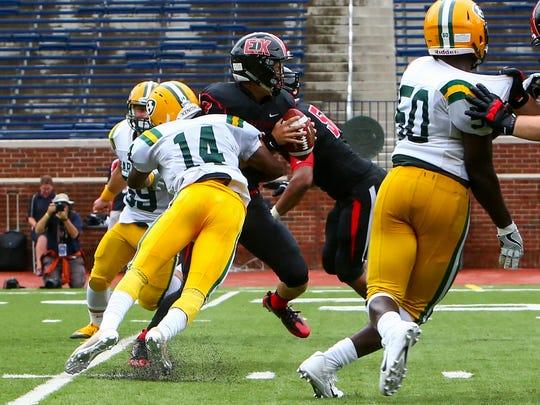 Junior outside linebacker Jerrin Harvey (14) rushes in to sack opposing quarterback Evan Maday.