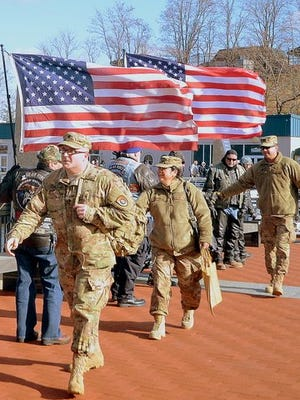 American flags and motorcycle riders greet Army soldiers arriving on the Battleship New Jersey Museum and Memorial pier for Thanksgiving dinner last year