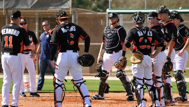 Miami Marlins catcher Jarrod Saltalamacchia listens to manager Mike Redmond explain proper technique for covering home plate in lieu of forthcoming regulations barring collisions.