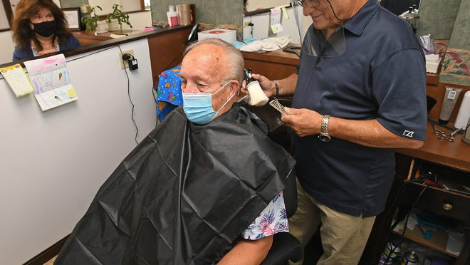 "Edward Palotas gets a haircut from Frank Romeo, 75, at right, at Frank A. Romeo's Family Hairstyling, 3725 Elmwood Ave. in Erie, on Thursday. Romeo is retiring after more than 50 years in the business in Erie. In the background, at left, is his wife, Eileen Romeo, 69. Palotas, 77, of Erie, has been a customer since 1964. He';s also Romeo's neighbor, and hopes Romeo will continue his haircuts for friends, possibly in his garage. ""I'll bring my own scissors. Or hedge trimmers,"" said Palotas."