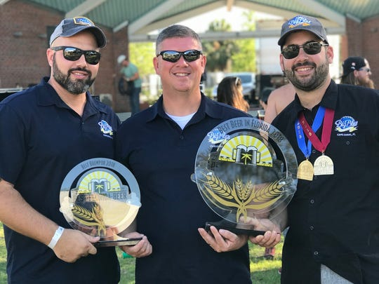 From left, Alexander Sarames, Joseph Termini and Phil Brittain show off the hardware Cape Coral's Big Blue Brewing won at Sunday's Best Florida Beer Championships in Tampa.