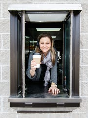 Owner Julie Sokolowski of Cafe Buzzz in Wales serves up a hot coffee from the drive-thru window on Friday, March 16, 2018. The establishment offers coffee drinks, breakfast and lunch sandwiches, salads, soups, blended smoothies and self serve frozen yogurt with all the toppings.