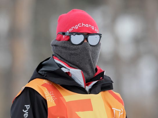 A race worker covers up from the cold during the men's 15km/15km skiathlon cross-country skiing competition at the 2018 Winter Olympics in Pyeongchang, South Korea, Sunday, Feb. 11, 2018. (AP Photo/Kirsty Wigglesworth)
