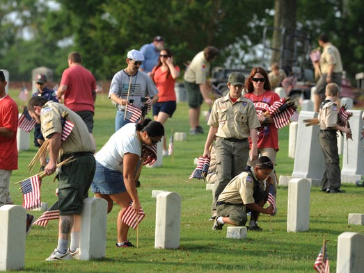 Volunteers place flags at grave markers Saturday morning at Barrancas National Cemetery in preparation for Memorial Day.