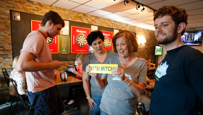 """Boone County Democratic Party Chairwoman Carole Register displays a """"Ditch Mitch"""" sticker during the group's monthly gathering at Lucky Duck Pub in Burlington."""