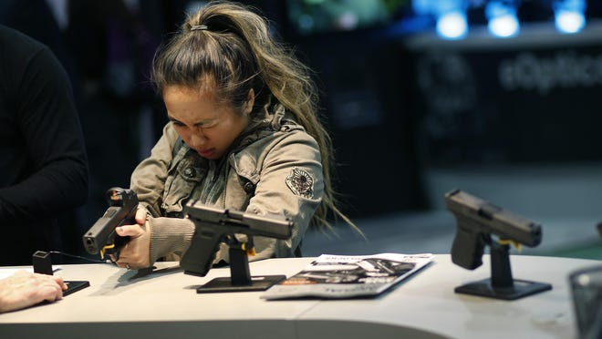 A woman looks at a handgun at the Glock booth at the Shooting Hunting and Outdoor Trade Show, Tuesday, Jan. 19, 2016 in Las Vegas.