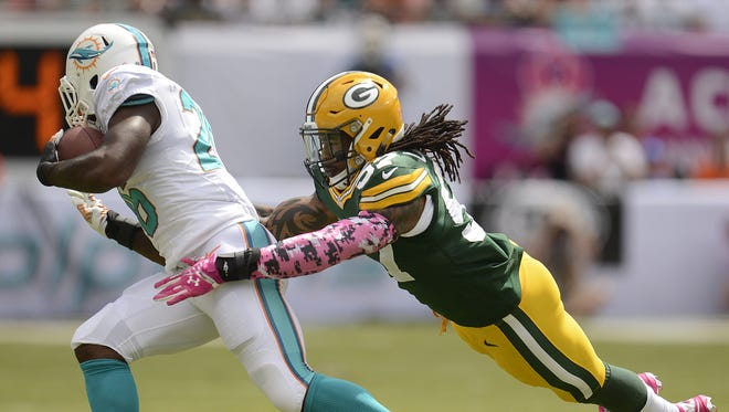 Green Bay Packers linebacker Jamari Lattimore (57) dives to tackle Miami Dolphins running back Lamar Miller (26) in the first quarter during Sunday's game at Sun Life Stadium.
