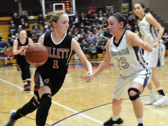Sydney Young of Gillett dribbles around Tiara Barber