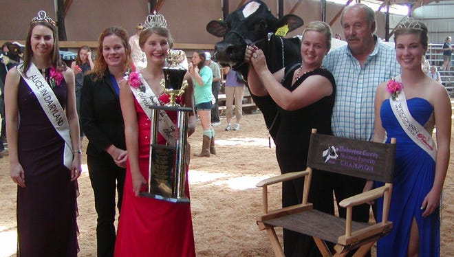 Handler Sara Feldmann (second from right)  and Ron Roskopf, owner of  winning entry Cow-Palace Fever So Real, and judge Molly Sloan (second from left) are joined with royalty  (from left)  Ann O'Leary 69th Alice in Dairyland, 2016 Sheboygan County Fairest of the Fair Makayla Klumpyan and Kati Kindschuh Wisconsin Holstein Association Princess.