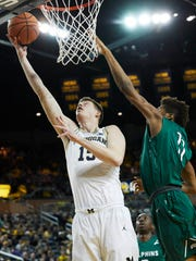 Michigan center Jon Teske (15) shoots against Jacksonville guard Jalyn Hinton (11) in the first half on Saturday, Dec. 30, 2017, at Crisler Center.