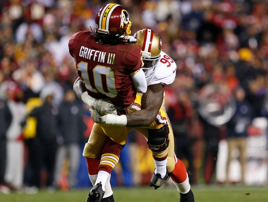 49ers linebacker Aldon Smith (99) crushes Redskins quarterback Robert Griffin III (10) on a second-quarter pass. San Francisco intercepted the pass.