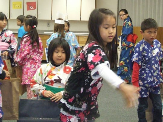 Second-grader Kanon Chudo plays ring toss Friday during