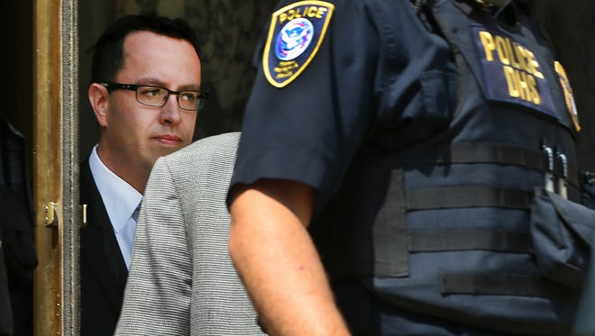 Surrounded by security, former Subway spokesperson Jared Fogle, left, walks out of the Federal Courthouse in Indianapolis on Wednesday, Aug. 19, 2015, after his hearing on charges of possessing and distributing child pornography and having sex with minors.