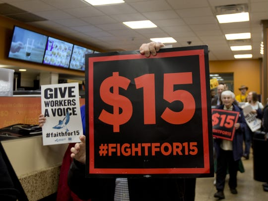 Supporters of a $15 minimum wage walk through a Dunkin'