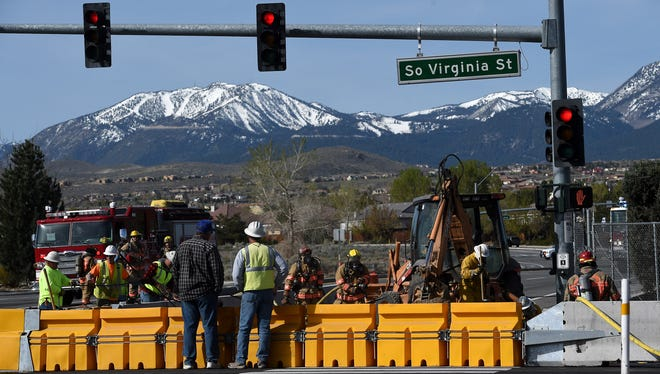 The Washoe County Fire Department works with NV Energy employees to safely deal with a gas leak to a service line caused by a backhoe at the intersection of South Virginia Street and Damonte Ranch Parkway in south Reno on April 9, 2015.
