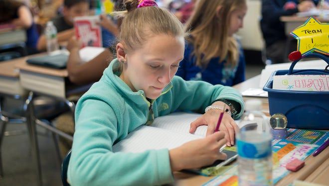 Marianna Gerdus, 11, writes in her notebook during a writing workshop at Woodrow Wilson Elementary School in Binghamton.