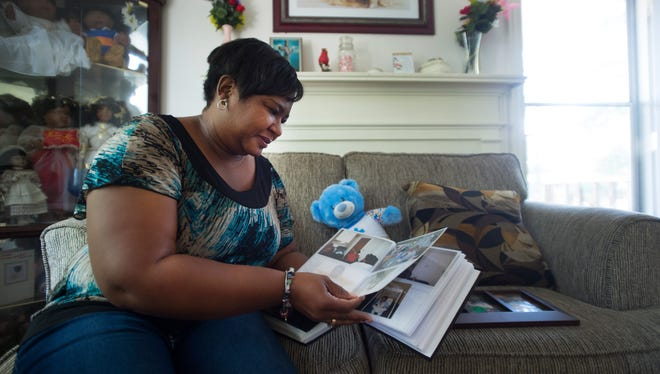 Michelle McCarroll flips through a photo album and looks at pictures of her brother, Jamie Rosemond, in her home on Monday, May 2, 2016.