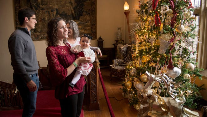 John Ustick with his wife, Leigh Ustick, holding Maggie Ustick, 8 months, of Bloomfield Township and Leigh's mother, Nanine Savoie of Birmingham, view the holiday decorations at Meadow Brook Hall on Thursday, Dec. 21, 2017. A photo of Nanine and Leigh was featured on the front page of the Free Press in 1987.