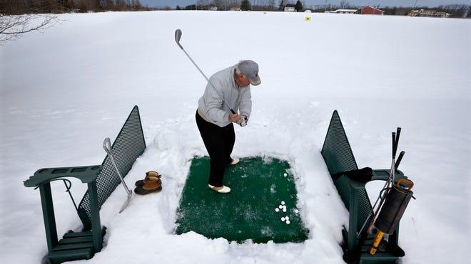 Rich Lukasik, of Whiting, N.J., hits practice golf shots in the snow on Feb. 19 in Cream Ridge, N.J.