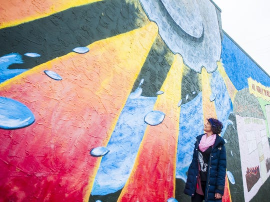 Michelle Chenoweth, member of Downtown Chicks, yoga instructor and cancer survivor, observes a Great Falls mural near Traci's Family Restaurant.