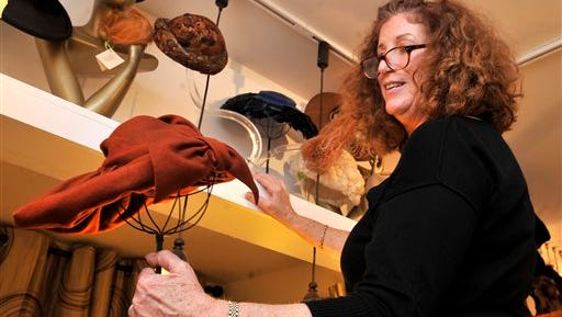 """Cindi  Ryland owner of Retropolitan, pulls a vintage rust wool hat from the shelf, showcasing the style of hats being using in the upcoming film, """"The Dressmaker"""" while at her shop in West Annapolis on  Dec. 17."""
