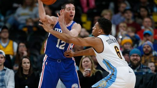 Philadelphia 76ers guard T.J. McConnell, left, passes the ball over Denver Nuggets guard Axel Toupane during the second half of an NBA basketball game Wednesday, March 23, 2016, in Denver. The Nuggets won 104-103. (AP Photo/David Zalubowski)
