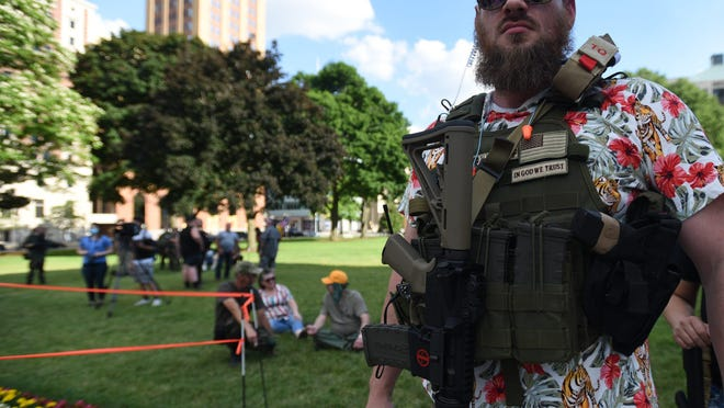 """Demonstrators rally during the """"American Patriot Rally: A well-regulated militia"""" at the Michigan State Capitol in downtown Lansing Thursday evening, June 18, 2020."""