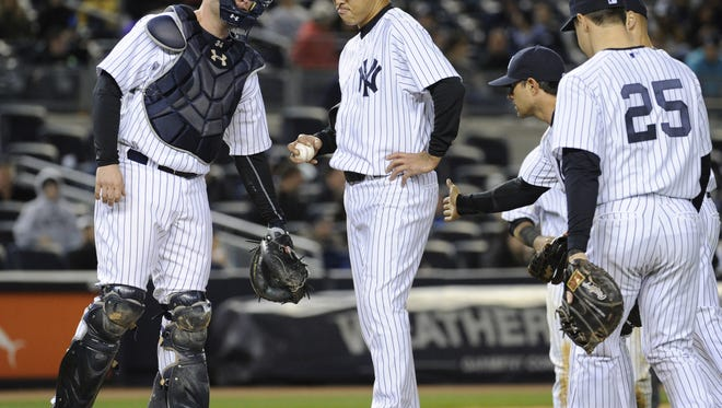 Yankees pitcher Hiroki Kuroda shows his frustration as catcher Brian McCann comes to the mound before Kuroda left the game during the fifth inning Friday night against the Angels.