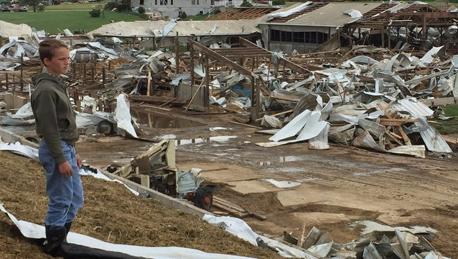 Daniel Zimmerman, 11, of Snover looks over the debris of  the destroyed barns at the de Vor dairy farm Tuesday, June 23, 2015 in Lamotte Township. The storm Monday night destroyed about a dozen barns and killed about 40 cows.