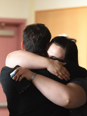 Lindsey Vorse embraces a former classmate on Tuesday at Livingstone Adventist Academy where a group of students gathered to remember the life of their friend, Joshua Robertson, who died died Monday following a longboarding accident.