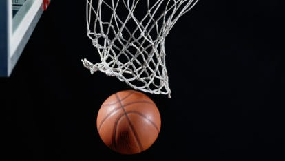 A stock image of a basketball going through a hoop.