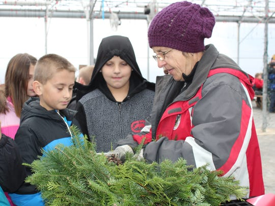 Longtime employee Lil Piatek shares tip on how to attach clusters of pine cones to a wreath.