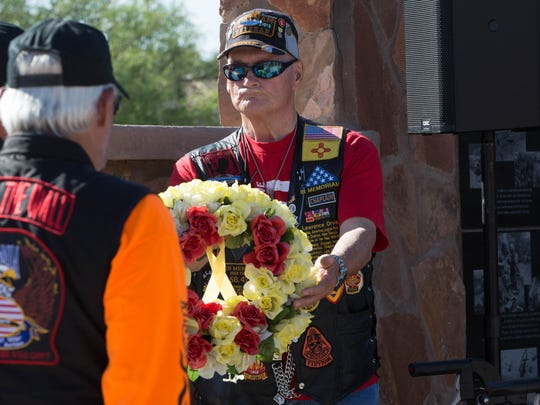 Lawrence Orvis, chaplain with the American Legion in Las Cruces, hands a wreath to Rich Pachecano, and Craig Corris, not shown, during a wreath laying ceremony at the Vietnam War Memorial at Veterans Memorial Park, Friday May 18, 2018. The wreath laying was part of Run For The Wall, a 10 day-motorcycle trip from California to Washington D.C., made up of  veterans and civilians wanting to honor prisoners of war an soldiers missing in action.