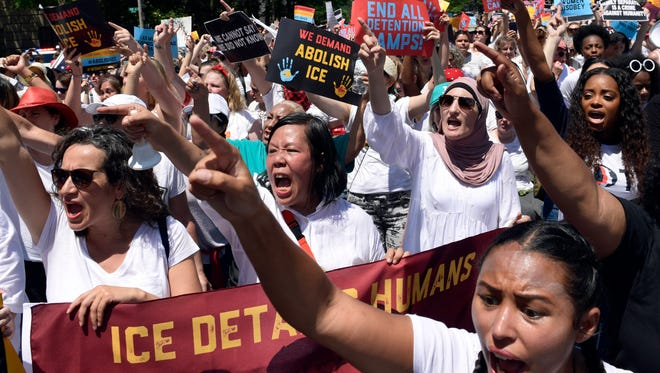 """Protesters shout """"shame"""" as they march past the Trump Hotel during an immigration rally in Washington, D.C., on June 28, 2018."""