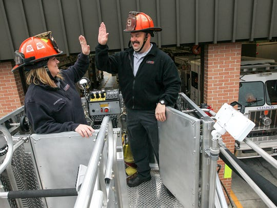 Courtney Brown, left, and Lt. Stephen Teske give each other a high-five after trying out the 100-foot ladder on a new $1.2 million 2017 Sutphen platform fire at the Clemson fire department.
