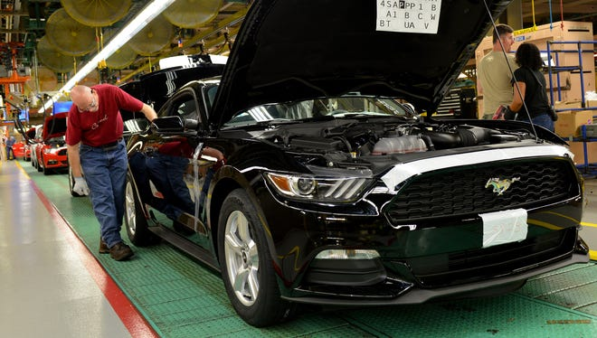 A worker inspects the new 2015 Ford Mustang, which begins production today in Flat Rock, Mich.