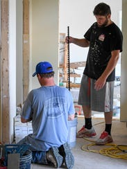 John Anderson (left) and David Cundiff lay tile in
