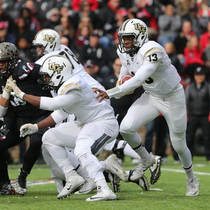 UCF quarterback Justin Holman carries the ball in the first half against the Cincinnati Bearcats on Oct. 31. The Knights are currently 0-10 and are having the worst season since 2004.