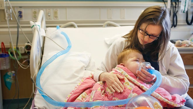 Jaime Miller calms her daughter, Eliza, 2, as she gives Eliza extra oxygen. The Millers live in Crystal City, Missouri, but Jaime has been staying at Ronald McDonald House, which is across the street from Cincinnati Children's Hospital Medical Center.