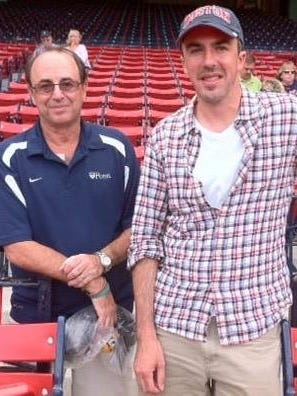 Richard Gelles, left, and son Jason at Fenway Park in 2011. Richard is holding a plastic bag containing a canister with the ashes of Jason's grandmother before releasing them in left field.