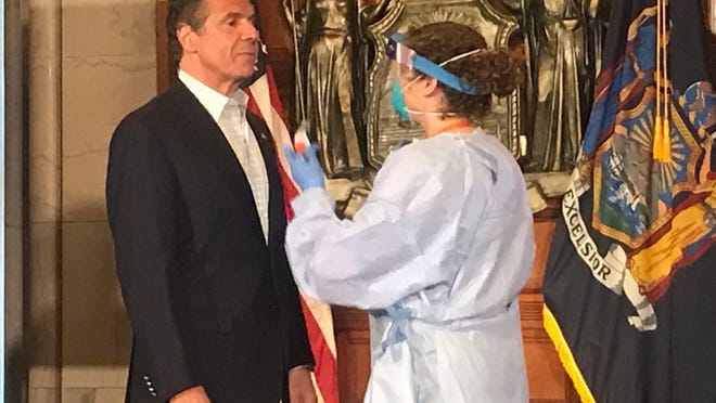 New York Gov. Andrew Cuomo gets ready for a COVID-19 test during his daily coronavirus briefing at the state Capitol in Albany; May 17, 2020.