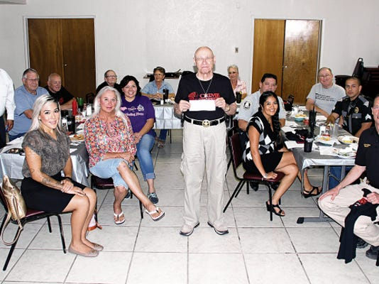 Bill Armendariz - Headlight Photo   Ben Friedman, standing in center, shows the 1,000 check Deming-Luna County Crime Stoppers received from the Deming Walmart Community Grants Foundation to help fight crime during Tuesday's monthly meeting.