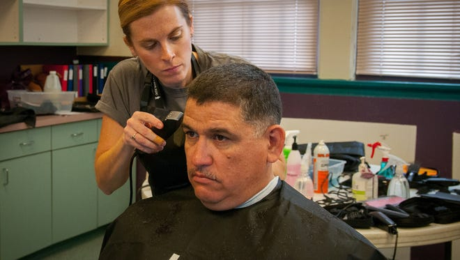 Veteran Antonio Roybal has his hair cut at no cost by Vista College cosmetology student Cecilia Trevino at the Las Cruces Veteran's Stand Down event at Alma d'Arte Charter High School on Saturday.