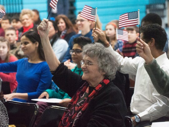 New U.S. citizen Marie Stewart waves the American flag during a U.S. Citizenship and Immigration Services naturalization ceremony at Marlton Elementary. Stewart, who lives in Toms River, has been in the U.S for 54 years.