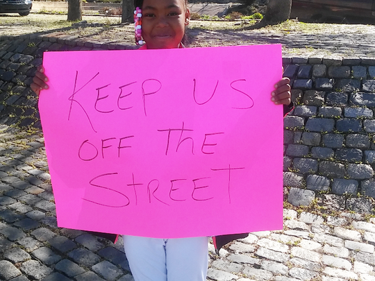 Nevaeh Cole holds up a sign at a recent car wash where children are trying to raise money to pay for a trip to Disney World this summer.
