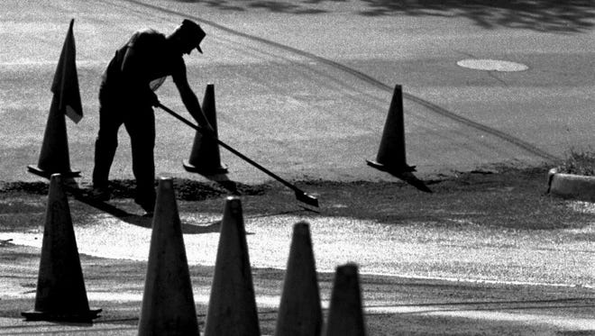 An earlier job: Ted Darrow of Cady Co, of Amsterdam, New York, smooths out asphalt sealer at the bottom corner of Hall and St. Peter Streets and Malletts Bay Avenue in Winooski. Photographed Tuesday, Aug. 23.