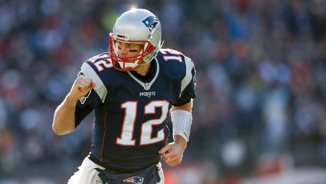 New England Patriots quarterback Tom Brady (12) celebrates after a touchdown during the first quarter against the Los Angeles Rams at Gillette Stadium.