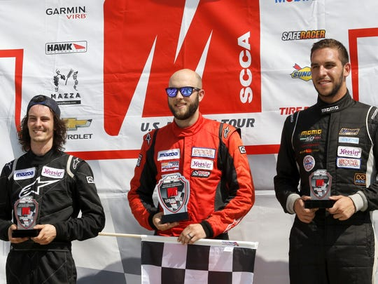 Spec Miata race winner Tyler Kicera (center) in victory