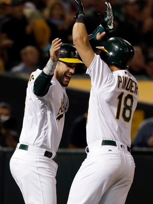 Oakland Athletics' Chad Pinder, right, celebrates after driving in teammate Trevor Plouffe, left, with a two-run home run against the Boston Red Sox during the fourth inning of a baseball game Thursday, May 18, 2017, in Oakland, Calif. (AP Photo/Marcio Jose Sanchez)